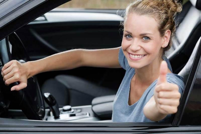 Frau verkauft Auto und hält Daumen nach oben